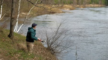 fisher : Mature man catches fish on the river.
