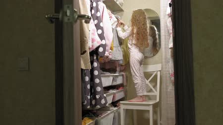 abiti appesi : Beautiful little girl chooses dress in home wardrobe. Beauty and fashion