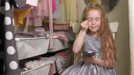 dressing room : Beautiful little girl puts makeup on face. Fashionable children.