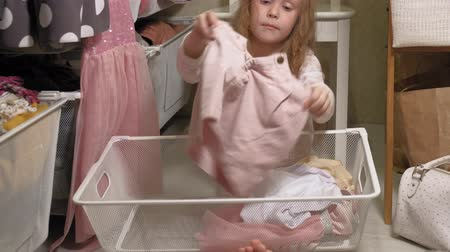 kasten : Little girl cleans up clothes in home wardrobe