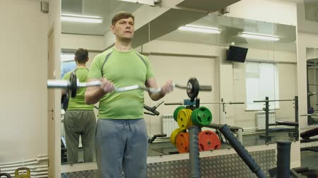 consciente : A overweight man lifts an ez barbell while standing at the gym. Exercise for biceps. Fitness. Healthy lifestyle.