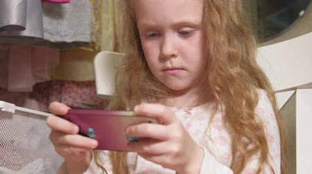 светлые волосы : Beautiful little girl uses the phone