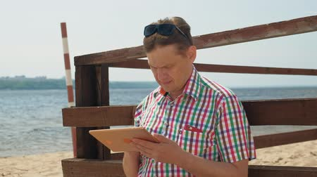 ebook : A man on the beach uses a computer tablet. Stock Footage