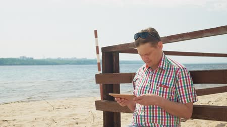 no exterior : A man on the beach uses a computer tablet. Stock Footage