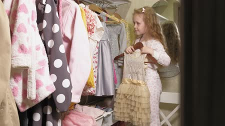 standlar : Beautiful little girl chooses dress in home wardrobe. Beauty and fashion