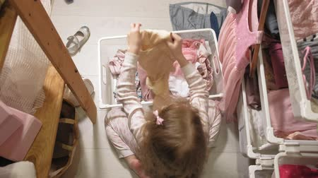 drawer : Little girl cleans up clothes in home wardrobe
