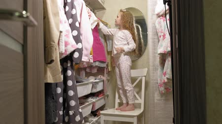 döntés : Beautiful little girl chooses dress in home wardrobe. Beauty and fashion