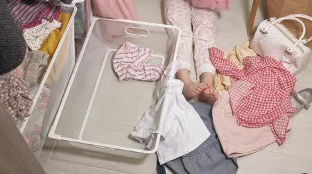 szervez : Little girl cleans up clothes in home wardrobe