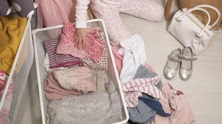 traje de passeio : Little girl cleans up clothes in home wardrobe