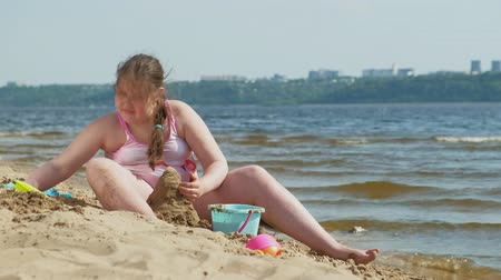 купальный костюм : Girl builds a sand castle on the river bank Стоковые видеозаписи