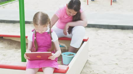 ón : Children use a computer tablet, walk on the playground Stock mozgókép
