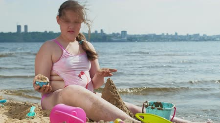 Łopata : Girl builds a sand castle on the river bank Wideo