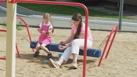 benches : Children use a computer tablet, walk on the playground Stock Footage