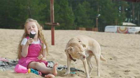 fagylalt : Girl eats ice cream and feeds the dog outdoors.