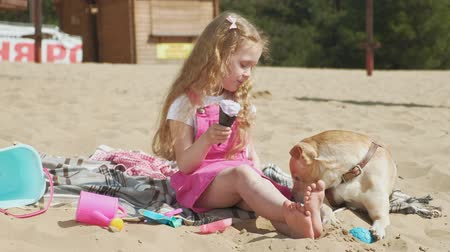 конусы : Girl eats ice cream and feeds the dog outdoors.