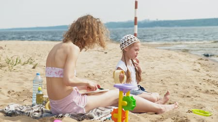 sand bank : mother with her daughter on a picnic by the river on a sunny day