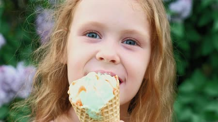 конусы : Little girl eats ice cream outdoors. Summer Стоковые видеозаписи