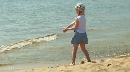 sand bank : Preschool girl walks by the river on a summer day