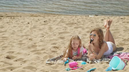sand bank : Mom and daughter on the river bank eat ice cream. Outdoor recreation