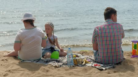 sand bank : A mature man in a plaid shirt with two girls are sitting on the sand by the river. Family outdoor activities