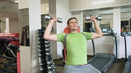 усилие : A man doing a bench press with dumbbells sitting with a straight grip in a fitness studio Стоковые видеозаписи