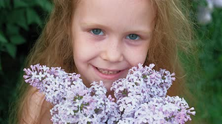 enjoys : A little girl outdoors in a park or garden holds lilac flowers. Lilac bushes in the background. Summer, park