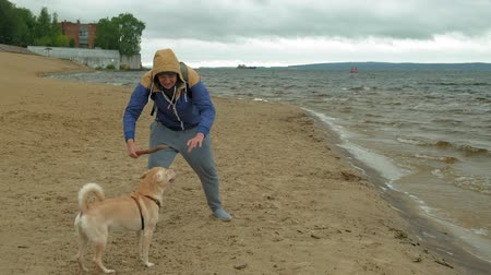 sand bank : A man plays with a dog by the river