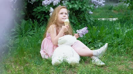 przedszkole : Little girl eats ice cream outdoors. Summer Wideo