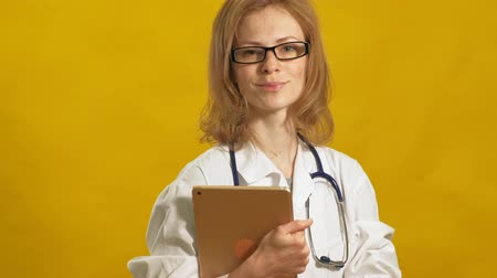 matraz : Young woman doctor. Yellow background. The concept of medicine.