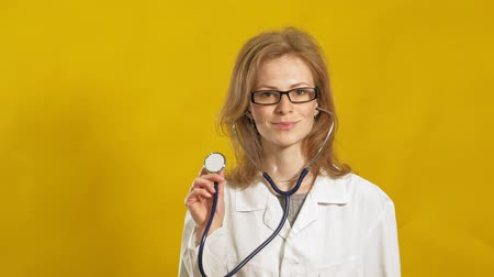 flasks : Young woman doctor. Yellow background. The concept of medicine.