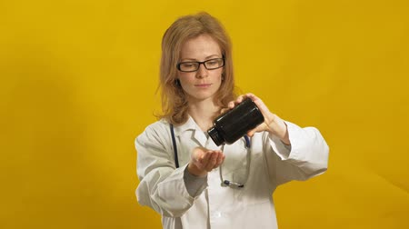 může : Young woman doctor. Yellow background. The concept of medicine.