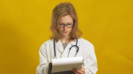 banka : Young woman doctor. Yellow background. The concept of medicine.