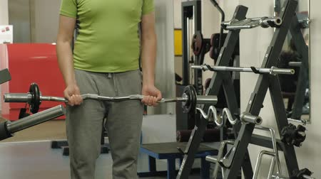 tense : A overweight man lifts an ez barbell while standing at the gym. Exercise for biceps. Fitness. Healthy lifestyle.