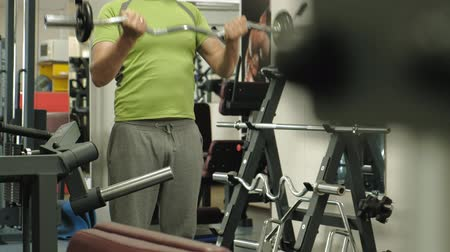 břišní : A overweight man lifts an ez barbell while standing at the gym. Exercise for biceps. Fitness. Healthy lifestyle.