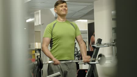 raises : A overweight man lifts an ez barbell while standing at the gym. Exercise for biceps. Fitness. Healthy lifestyle.