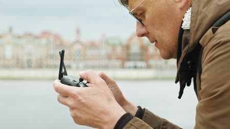 controles : Man controls the drone outdoors.
