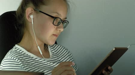 genius : Teen girl uses tablet with headphones. Evening time Stock Footage