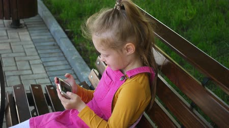 pré escolar : A smiling girl a preschool age , uses the phone outdoors in the park. Sunny summer day. Stock Footage