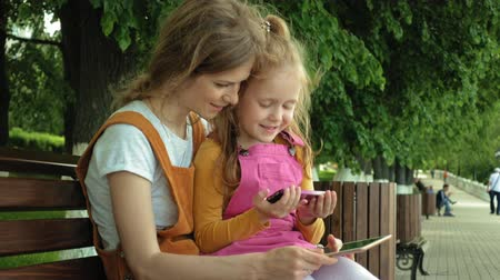 во : Mom and daughter use gadgets in the open air. Summer