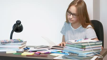 papeteria : A teenager girl with glasses is sitting at a school desk. learning concept