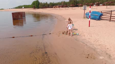 brotos : Mom and daughter are playing on the beach, building a sand castle. Summer sunny day. vacation. Aerial shooting