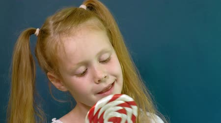lollipop : Little girl with a lollipop on a blue background. Close up portrait