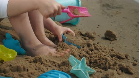 купаться : Girl child plays with sand on the beach using molds figurines. Sunny summer day. vacation
