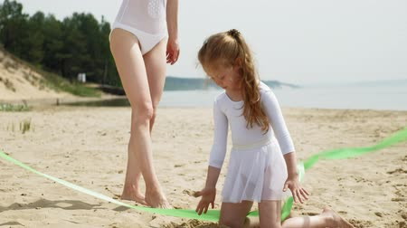 targi : mother and daughter in white bathing suits dancing with gymnastic ribbon on a sandy beach. Summer, dawn