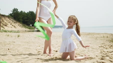 balanceamento : mother and daughter in white bathing suits dancing with gymnastic ribbon on a sandy beach. Summer, dawn