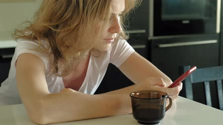 desgrenhado : The woman in the kitchen uses the tablet, just woke up. Breakfast. Early morning Stock Footage