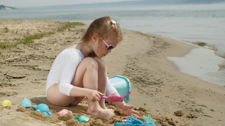 kalıp : Girl child plays with sand on the beach using molds figurines. Sunny summer day. vacation