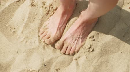 their : Feet are on the sand near the water. Beach. Summer sunny day Stock Footage