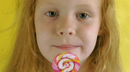 леденец : Little girl with a lollipop on a Yellow background. Close up portrait Стоковые видеозаписи