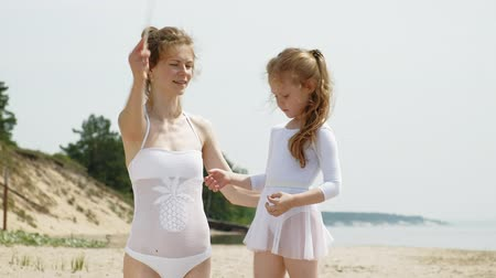 acrobata : mother and daughter in white bathing suits dancing with gymnastic ribbon on a sandy beach. Summer, dawn